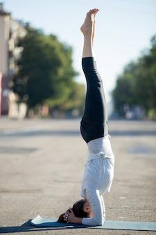 Гибкая женщина в позе йоги на открытом воздухе