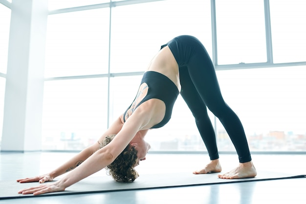 Flexible woman on mat doing yoga next to a large window