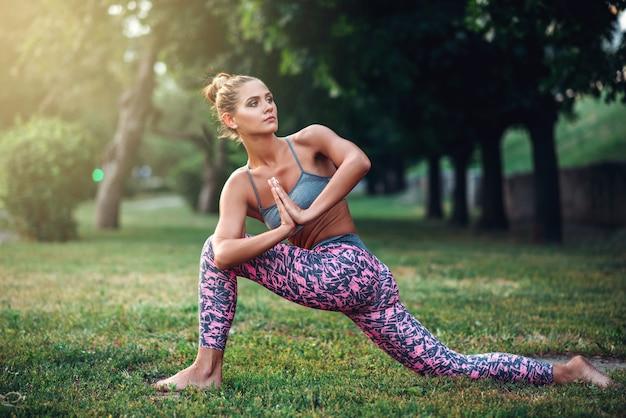 Гибкая женщина медитирует, обучение йоге на траве в летнем парке. утренняя йогическая медитация