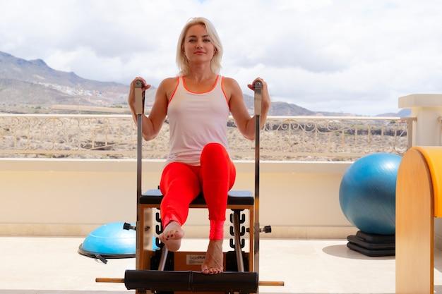 Гибкая женщина, практикующая пилатес в летний день на специальном оборудовании, молодая фитнес-леди растягивает тело с реформатором во время тренировки на террасе на открытом воздухе с потрясающим видом на горы. концепция спорта