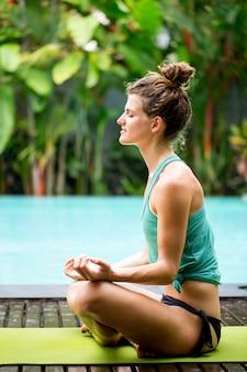 Flexible woman practicing yoga in backyard