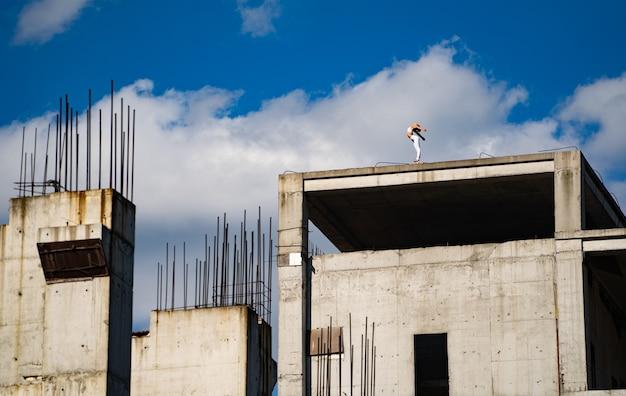 Гибкая женщина, стоящая на краю строящегося здания. концепция свободы, отваги и силы воли.