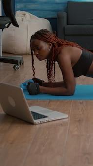 ヨガスポーツの練習を練習しているスポーツウェアを身に着けている黒い肌を持つ柔軟な女性