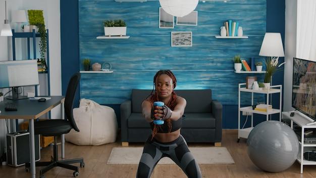 아령을 사용하여 쪼그리고 앉는 운동을하는 검은 피부를 가진 유연한 여성