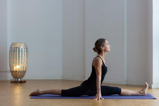 Flexible woman with split legs on monkey pose