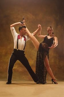 스튜디오에서 pasadoble 춤을 추는 유연한 젊은 부부. 매력적인 남자와 여자의 패션 초상화입니다. 열정. 사랑