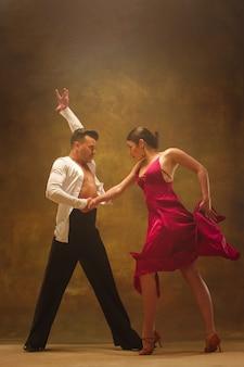 スタジオでパソドブレを踊る柔軟な若いカップル。魅力的な男性と女性のファッションの肖像画