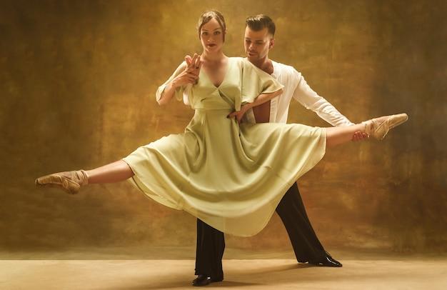 스튜디오에서 탱고 춤을 추는 유연한 젊은 부부. 매력적인 남자와 여자의 패션 초상화입니다. 열정. 사랑