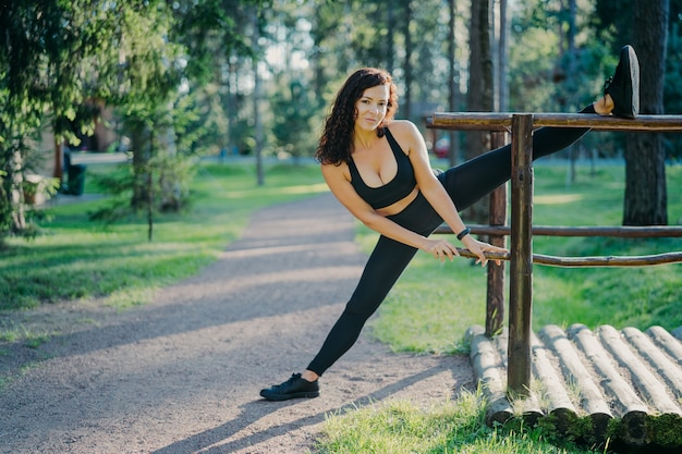 Flexible young curly woman wears black top leggings and sneakers, stretches legs