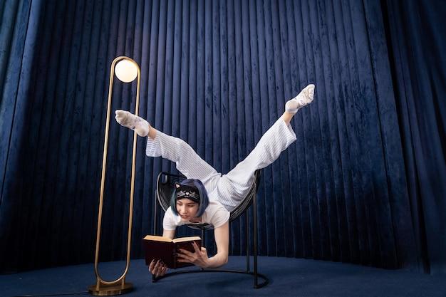 Гибкая молодая девушка в пижаме творчески читает книгу в помещении, концепция изучения индивидуальности и саморазвития