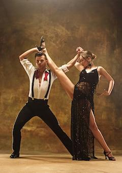 스튜디오에서 탱고 춤을 추는 유연한 젊은 현대 부부. 매력적인 춤 커플의 패션 초상화입니다. 남자와 여자. 열정. 사랑. 완벽한 피부 얼굴과 메이크업. 인간의 감정 - 사랑과 열정