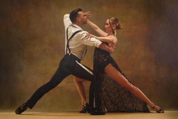 Flexible young modern couple dancing tango in studio. fashion portrait of attractive dancing couple. man and woman. passion. love. perfect skin facial and make-up. human emotions - love and passion