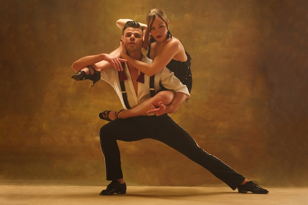 Flexible young modern dance couple posing in studio