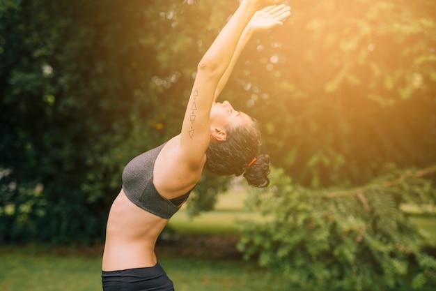 Flexible young woman exercising in the garden