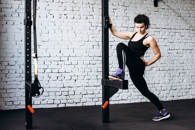Flexible young woman in the gym against white brick background