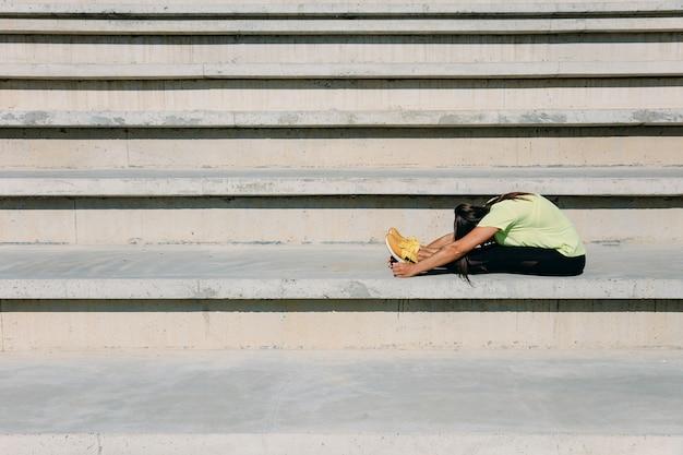 Гибкая молодая женщина с темными волосами, растягивая тело на шагах на открытом воздухе.