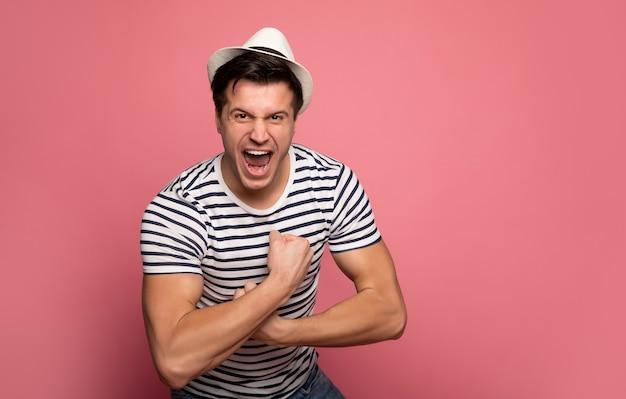 屈曲。縞模様のtシャツと白い帽子をかぶった強い男。カメラを見て、叫び、上腕二頭筋を見せています。