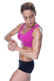 ピンクのスポーツブラジャーでflexing女性のボディービルダー