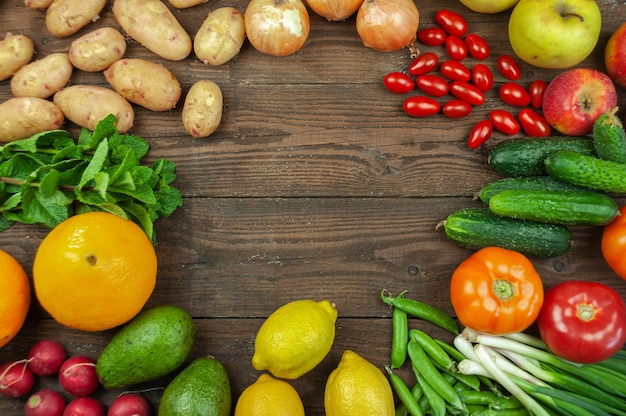 Flexitana 다이어트 개념입니다. 모듬된 신선한 유기농 야채와 과일이 있는 구성입니다. 텍스트를 위한 장소입니다. 오이, 토마토, 무, 아보카도, 완두콩, 감자, 레몬, 양파입니다. 어두운 나무 배경에 음식입니다.