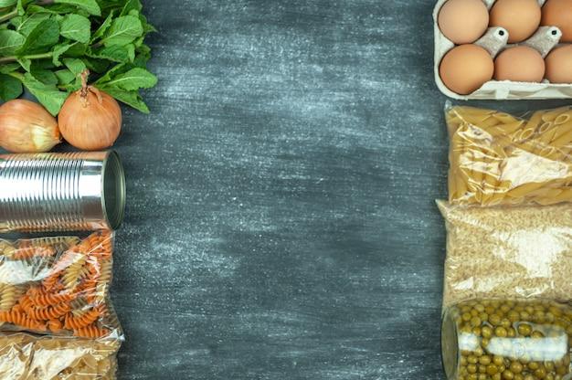 Flexitana 다이어트 개념입니다. 모듬된 신선한 유기농 야채와 과일이 있는 구성입니다. 텍스트를 위한 장소입니다. 민트, 완두콩, 양파, 계란, 쌀, 시리얼, 파스타, 통조림 식품입니다. 흰색 분필로 검은 배경에 음식입니다.