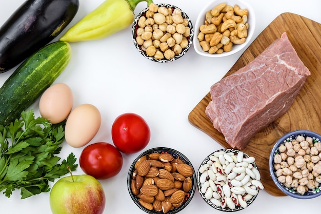 신선한 야채, 생고기, 계란, 콩과 식물, 견과류, 흰색 표면에 과일, 평면도, 근접 촬영으로 flexitarian 다이어트