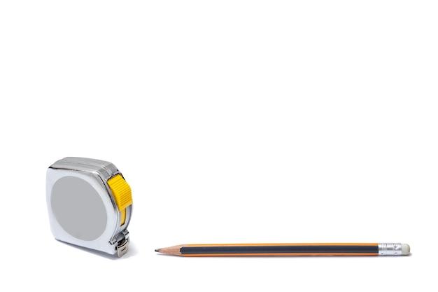 Flexometro plateado con la cinta metrica extendida y un lapiz al costado con fondo blanco