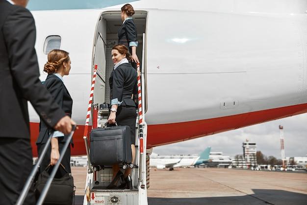 客室乗務員とスチュワーデスがはしごを上って飛行機のジェット機に向かっています。現代の旅客機。手荷物を持っている男性と女性は制服を着ています。チームワーク。民間商用航空。空の旅のコンセプト