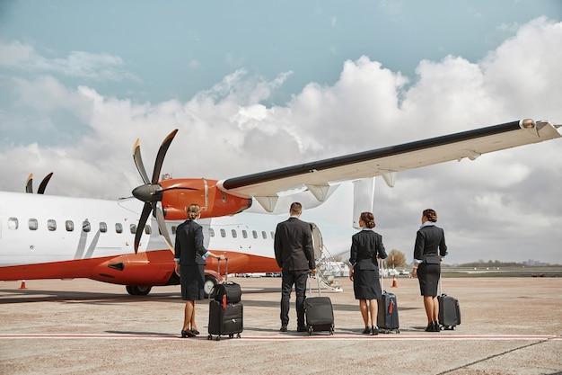 飛行機のジェット機の前に滑走路に立っている客室乗務員とスチュワーデス。現代の旅客機。手荷物着用の制服を着た男性と女性の背面図。チームワーク。民間航空。空の旅のコンセプト