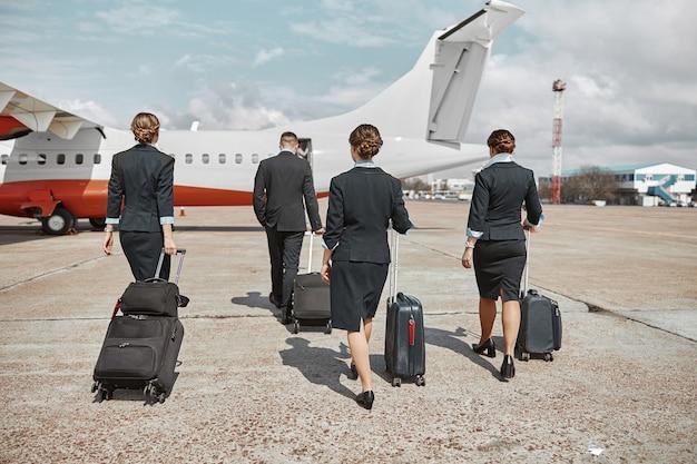 客室乗務員とスチュワーデスは滑走路を歩いて飛行機のジェット機に向かいます。現代の旅客機。手荷物着用の制服を着た男性と女性の背面図。チームワーク。民間航空。空の旅のコンセプト