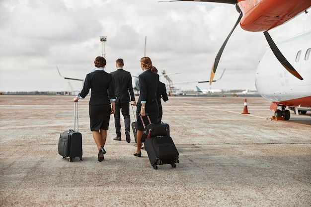 飛行機のジェット機の近くの滑走路を歩いている客室乗務員とスチュワーデス。現代の旅客機。手荷物着用の制服を着た男性と女性の背面図。チームワーク。民間航空。空の旅のコンセプト