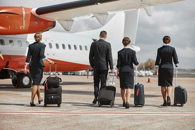 客室乗務員とスチュワーデスが滑走路を歩いて飛行機のジェット機に向かいます。現代の旅客機。手荷物着用の制服を着た男性と女性の背面図。チームワーク。民間航空。空の旅のコンセプト