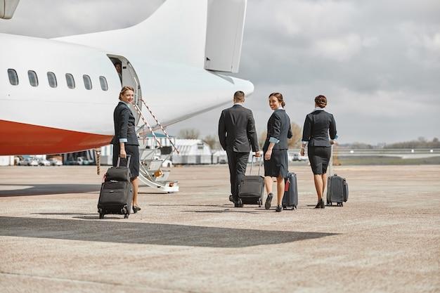 客室乗務員とスチュワーデスが滑走路を歩いて飛行機のジェット機に向かいます。現代の旅客機。荷物を着た男女の背面図は制服を着ています。チームワーク。民間航空。空の旅のコンセプト