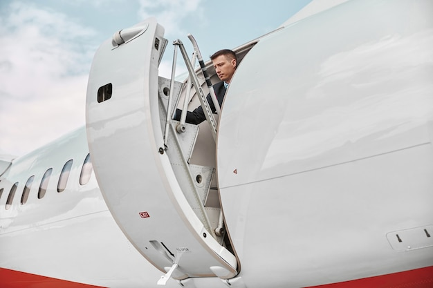 Flight attendant closed door of private airplane jet. modern passenger plane. serious mixed race man wear uniform. sunny daytime. civil commercial aviation. air travel concept