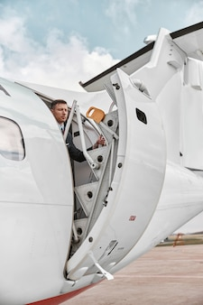 Flight attendant closed door of private airplane jet. modern passenger plane. serious multiracial man wear uniform. sunny daytime. civil commercial aviation. air travel concept