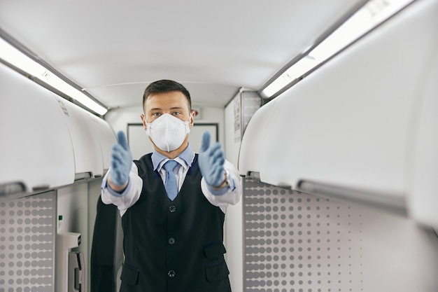 Flight attendant conducting safety instruction to passengers in cabin of airplane jet. modern plane interior. man wear uniform, latex gloves and medical mask. civil aviation. air journey concept