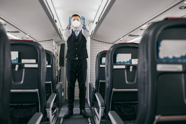 Flight attendant conducting safety instruction to passengers in cabin of airplane jet. modern plane interior. man wear uniform, latex gloves and medical mask. civil aviation. air travel concept