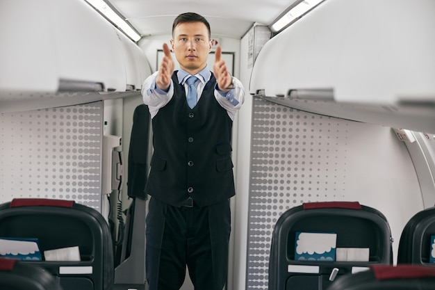 Flight attendant conducting safety instruction to passengers in cabin of airplane jet. modern plane interior. mixed race man wear uniform. civil commercial aviation. air travel concept