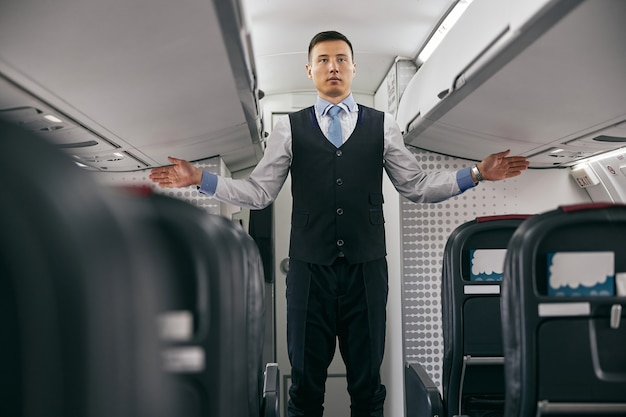 Flight attendant conducting safety instruction to passengers in cabin of airplane jet. modern plane interior. multiracial man wear uniform. civil commercial aviation. air travel concept