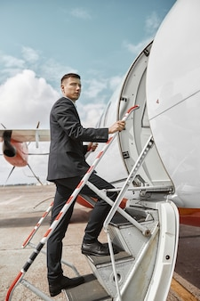 Flight attendant going up on ladder to airplane jet. modern passenger plane. serious multiracial man wear uniform. sunny daytime. civil commercial aviation. air travel concept