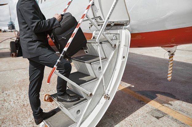 Flight attendant going up with baggage on ladder to airplane jet. modern passenger plane. cropped image of man wear uniform. sunny daytime. civil commercial aviation. air travel concept