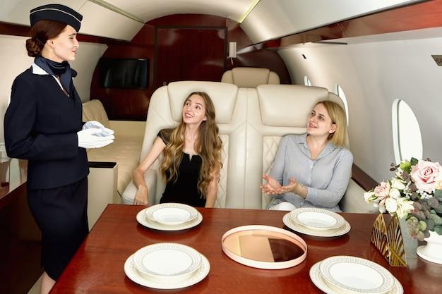 飛行機の客室乗務員がビジネスクラスの女性の乗客と話している。