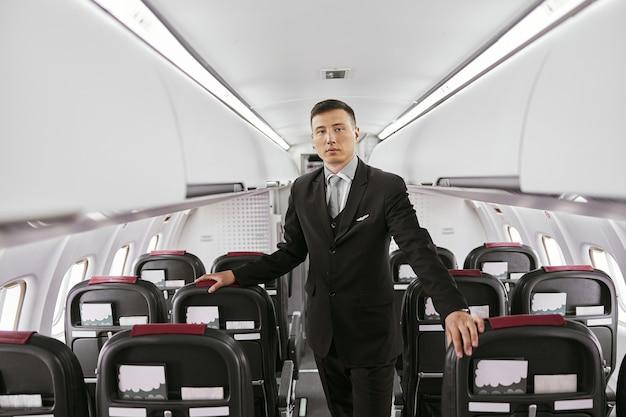 飛行機のジェット機の客室乗務員。モダンな飛行機のインテリア。多民族の男性は制服を着てカメラを見ています。民間商用航空。空の旅のコンセプト