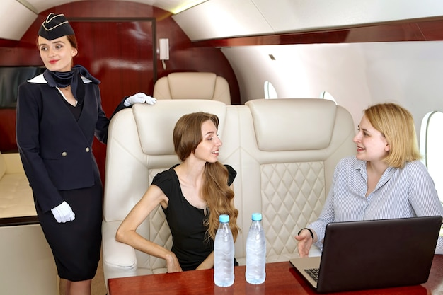 Flight attendant is standing inside business jet near seats with passengers of first class who are talking while watching film on laptop.