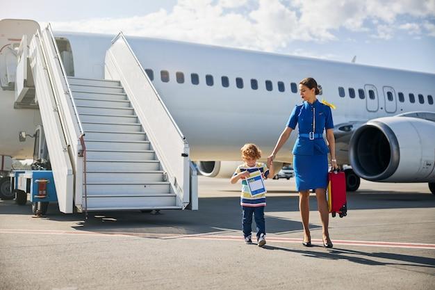 Flight attendant leading an unattended boy through the runway