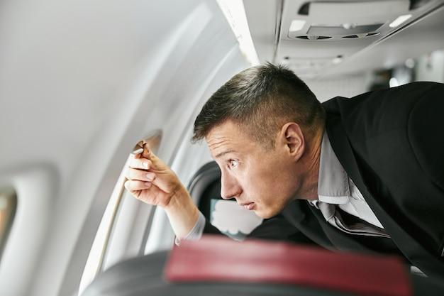 飛行機のジェット機の客室の窓から見ている客室乗務員。モダンな飛行機のインテリア。多民族のマンウェアユニフォームのプロフィール。民間商用航空。空の旅のコンセプト