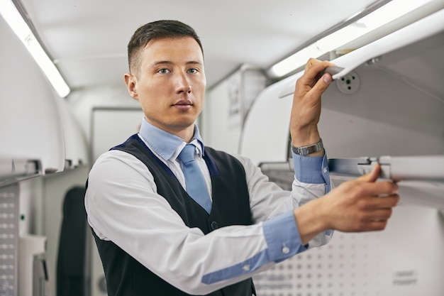 Flight attendant opening shelf in passenger cabin of airplane jet. modern plane interior. serious multiracial man wear uniform and looking at camera. civil commercial aviation. air travel concept
