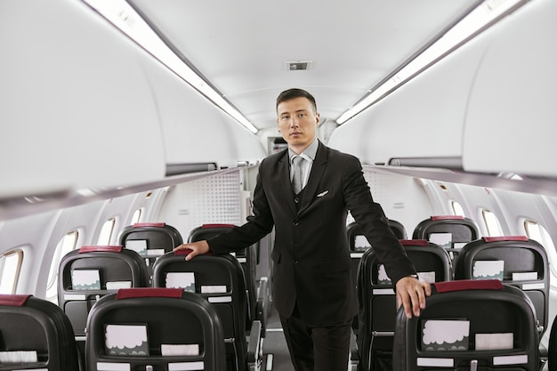 Flight attendant in passenger cabin of airplane jet. modern plane interior. multiracial man wear uniform and looking at camera. civil commercial aviation. air travel concept