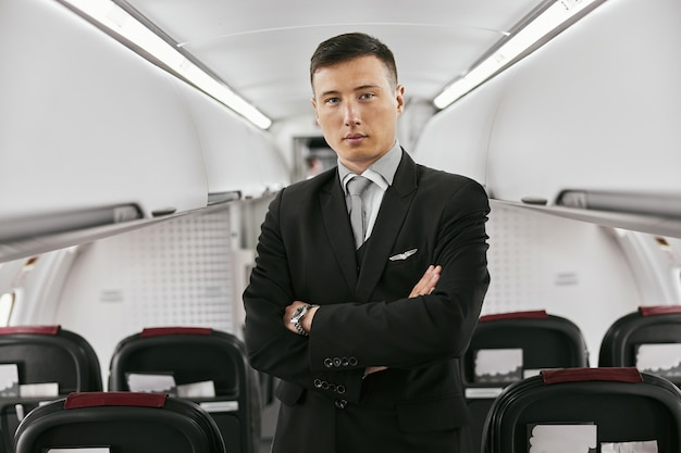 Flight attendant in passenger cabin of airplane jet. modern plane interior. multiracial man with crossed arms wear uniform and looking at camera. civil commercial aviation. air travel concept