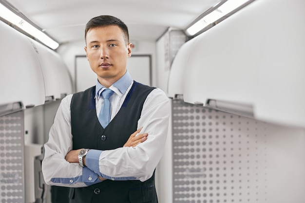 Flight attendant in passenger cabin of airplane jet. modern plane interior. serious multiracial man with crossed arms wear uniform and looking at camera. civil commercial aviation. air travel concept