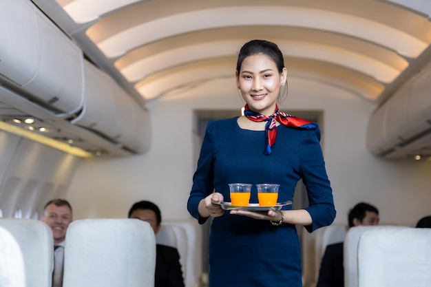Flight attendant serving, asian female flight attendant serving drink to passengers on airplane, cabin crew or air hostess working in airplane.